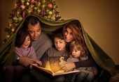 Big family reading interesting magic story in Xmas eve, happy parents with cheerful children covered
