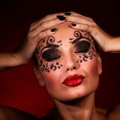 Closeup portrait of sexy seductive female with closed eyes and luxury makeup isolated on dark red ba