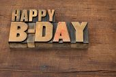 happy b-day (birthday) - text in vintage letterpress wood type on a grunge wooden background