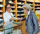 Pharmacist Serving A Senior Lady