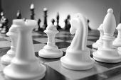 picture of chessboard  - Game of chess with chess pieces lined up on their squares on either side of the board ready for a challenge with selective focus to one white pawn - JPG