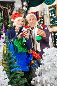 Senior couple in Santa hats shopping for Christmas decorations in store