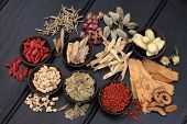 Chinese herbal medicine selection in wooden bowls and loose.