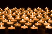 Large Group Of Burning Candles At A Black Background