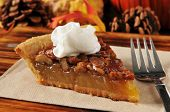 stock photo of pecan  - A slice of pecan pie on a holiday setting - JPG