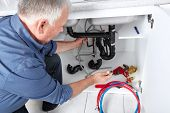 image of plumber  - Hands of professional Plumber with a wrench - JPG