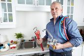 stock photo of pipe wrench  - Plumber in kitchen with a wrench - JPG