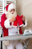 Funny Santa Claus ironing his pants that have shrunk