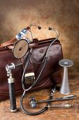 Doctor's bag and antique medical instruments such as stethoscope, reflex hammer and head mirror