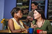 image of patron  - African and European women in a coffee house talking