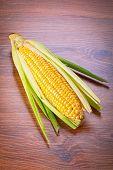 Fresh corncob on wooden table