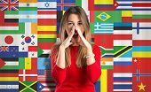 stock photo of shout  - Young girl shouting something over flags background - JPG