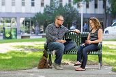picture of sitting a bench  - Male and female students with digital tablets sitting on bench at university campus - JPG