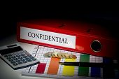 The word confidential on red business binder on a desk