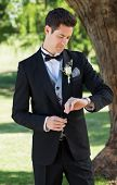 Young handsome groom checking time in garden