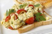 Scrambled egg on toast with cherry tomatoes, parsley and pepper. Cooking in a bain marie allows the