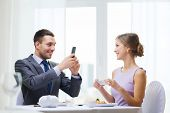restaurant, couple, technology and holiday concept - smiling man taking picture of wife or girlfrien