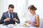 restaurant, couple, technology and holiday concept - smiling couple taking picture of sushi with sma poster