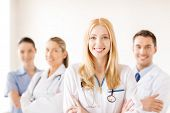 healthcare and medicine concept - attractive female doctor or nurse in front of medical group in hos