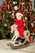 Little smiling girl dressed in santa suit sits on rocking horse under Christmas tree on furry rug