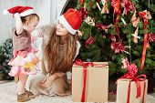 Two girls in santa caps on furry rug among gift boxes under Christmas tree in room poster