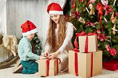 Teenage girl and little boy in santa caps sit on furry rug under Christmas tree untying ribbon  on g