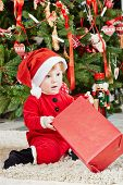 Little girl dressed in santa suit sits under Christmas tree on furry rug, holding red gift box poster
