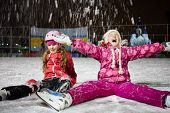 Two little girls sit on skating rink ice in evening under falling snow