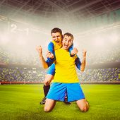 soccer or football players are celebrating goal on stadium, warm colors toned