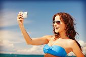 picture of happy woman with phone on the beach