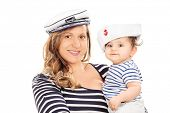 Mother and her baby daughter in sailor uniform isolated on white background
