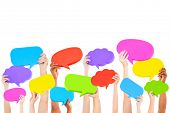 image of debate  - Hands holding multi colored speech bubbles - JPG
