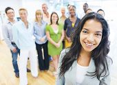 Beautiful Young Latin Woman Standing In Front of Crowd at Office