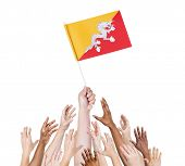 Diverse Multiethnic Hands Holding and Reaching For The Flag of Bhutan