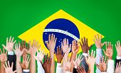 Group of Multi-Ethnic Arms Raised With Flag of Brazil