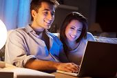 Young Couple At Home With Laptop