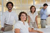 Portrait of a smiling young businesswoman with colleagues in background at office
