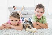 Siblings lying on rug with yorkshire terrier smiling at camera at home in the living room