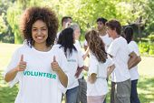Portrait of confident female volunteer showing thumbs up with friends disucssing in background