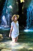 Beautiful young woman standing at the lake near waterfall in white dress and straw hat