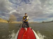 mature male paddler in wetsuit and life jacket enjoying workout on a stand up paddleboard (SUP), win