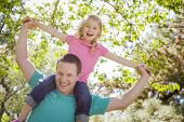 Cute Young Girl Rides Piggyback On Her Dads Shoulders Outside at the Park.