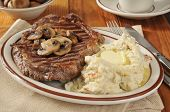 stock photo of sauteed  - A grilled rib steak with sauteed mushrooms and mashed potatoes infused with savory herbs