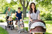 Portrait of beautiful mother pushing baby stroller in park with friends and children in background