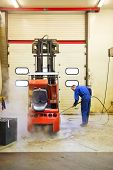 Worker, cleaning a forklift inside out, using a high pressure water jet in a maintenance workshop