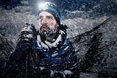 Adventure mountain man in snow expedition with climbing gear and determination