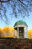 Pavilion In A Park With Yellow Birch Tree And Blue Sky On Background