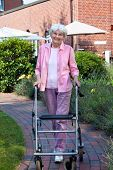Happy Elderly Woman Using A Walking Aid