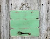 Blank green sign with bronze antique skeleton key hanging on rustic wooden door