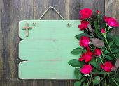 stock photo of funeral home  - Green blank sign with wooden cross and red flowers hanging on wood background - JPG